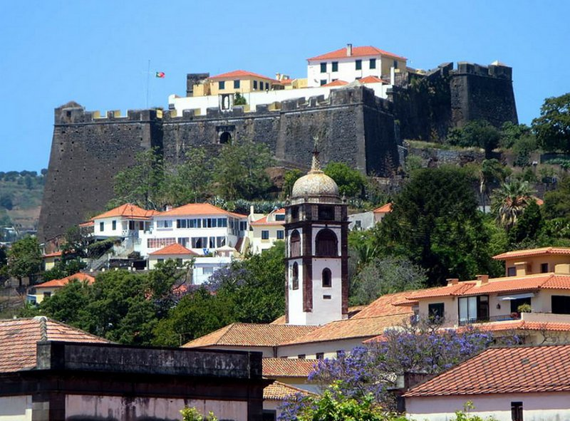 The tower of the Paróquia de São Pedro points at the early 17th century Fortaleza do Pico in Funchal, Madeira. by David Stanley
