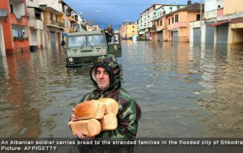 An Albanian soldier carries bread to the stranded families in the flooded city of Shkodra