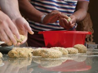 Making zucchini fritters at Vamos - courtesy the village's Facebook