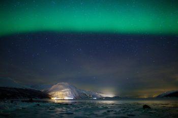 Green aurora borealis over a frozen fjord© spumador