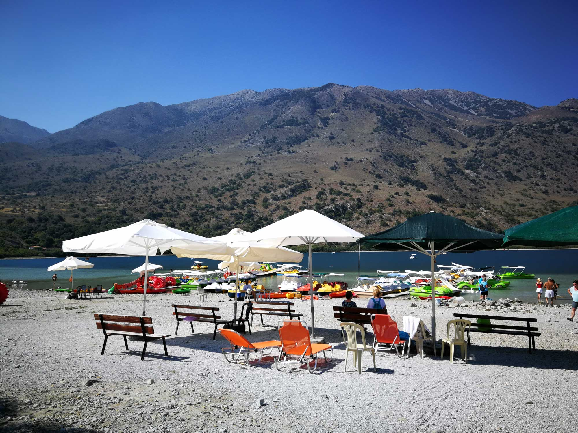 Lake Kourna beach with umbrellas and sun-loungers.