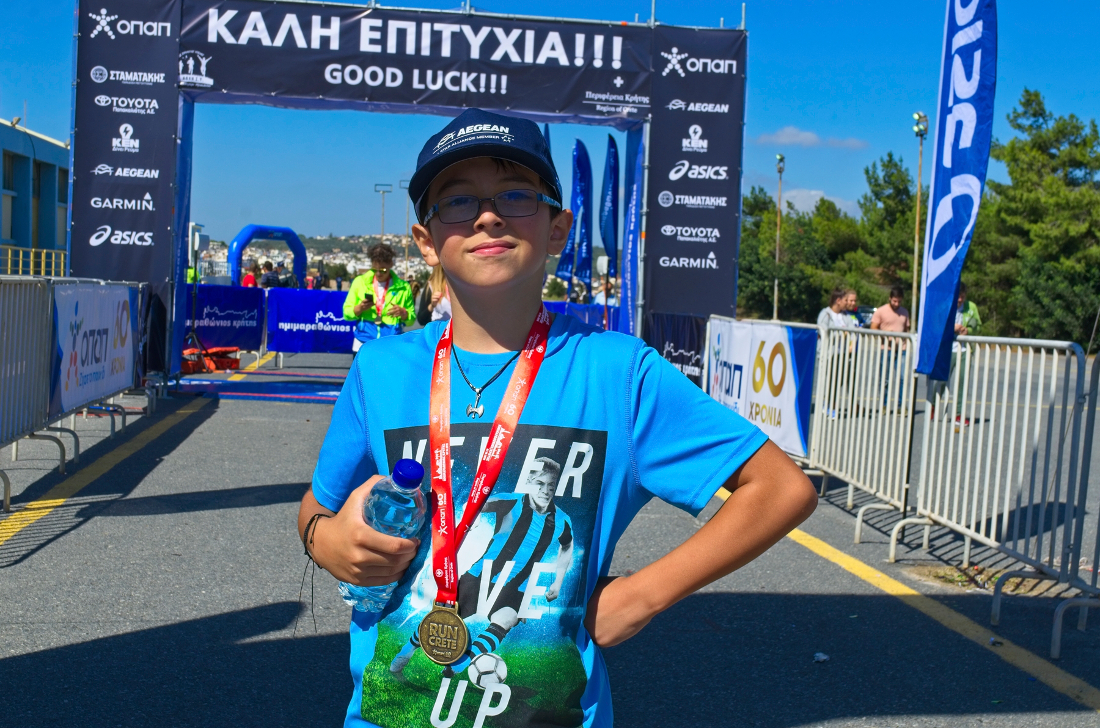 Our son, Paul Jules Butler shows off his Crete Half Marathon medal for participating in the 5k run